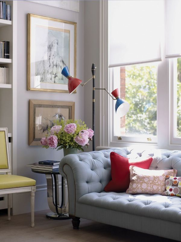 I like the mixture of styles and textures here. The romance of the flowers, the curved lines of the sofa with punches of red and blue and funky pillows. This looks stylish yet comfortable and inviting. LOVE<3