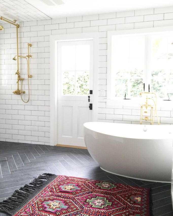 White subway tile bathroom, brass fixtures, woven rug + freestanding bathtub, bathroom design
