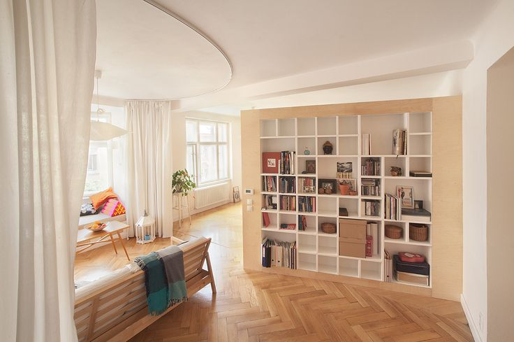 apartment interior with renovated parquet floor, plywood inbuilt furniture and a curtain for division of living zones