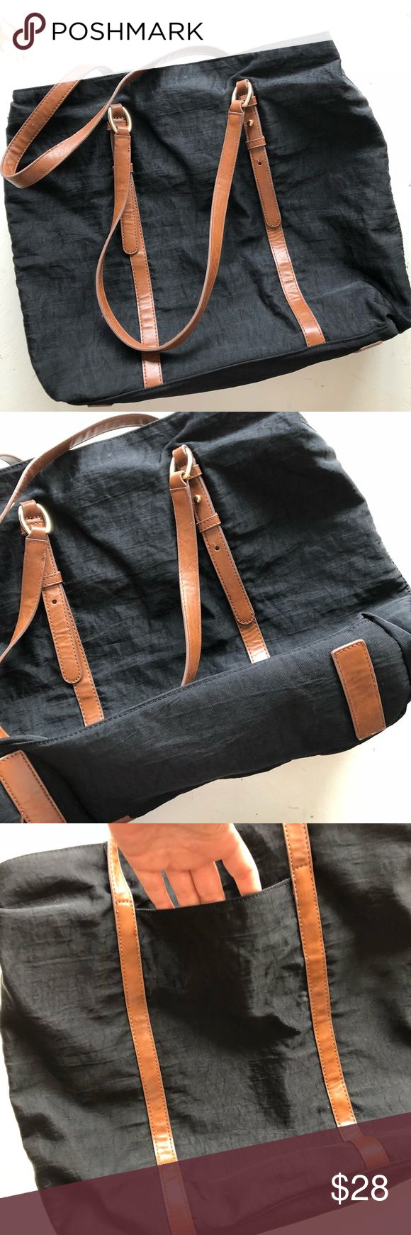 "Banana Republic black nylon tote bag Banana republic carry-to-work tote. Perfect for days at the office. Waterproof spot-cleanable nylon fabric, faux leather brown trim. Multiple compartments for all your essentials. Exterior is in great shape, some ink stains on bottom of lining. Tote is 16"" by 18"" Banana Republic Bags Totes"