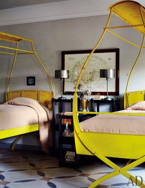 Twin steel beds in the guest room of a fanciful renovated farmhouse in Italy.