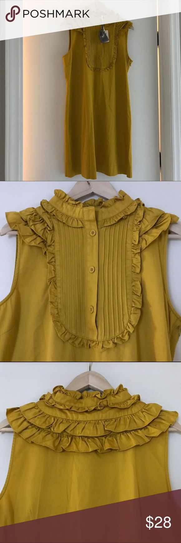 "NWT Fossil Mustard Yellow Dress, Size M NWT Fossil mustard gold dress. Size M. Sleeveless with side zip. Collar, lapel, and front of chest feature lovely ruffles. The ruffles extend round the back of the neck. The front of chest also has a three button closure and pleats. 100% cotton. This is a beautiful, comfortable dress with lots of stylish details. It screams ""autumn."" Fossil Dresses Mini"