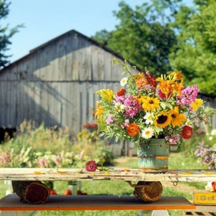 Outdoor entertaining with large colorful arrangements and plank tables.  Pioneer classics.