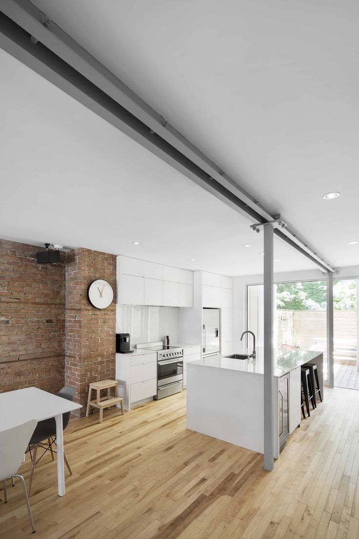 All-white kitchen in Quebec, offset by a brick wall