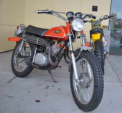"""The iconic Yamaha DT. Many dirt bike careers launched via these bikes during the early to mid '70s. A few of these buzzed around my childhood era neighborhood, much to the lust of motorcycle-less me. A friend occasionally let me ride his 100cc model around the backyard, heady stuff for a 12 year old. Thanks Ray Westcott, wherever you now may be. I still remember roosting through the """"puddle"""" in your yard, that turned out to be a leaky septic tank. The stuff dreams are made of."""