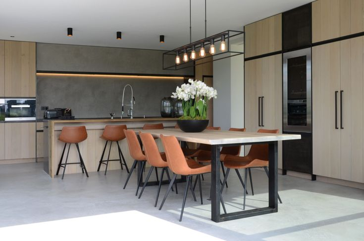 Tijdloze keuken door de combinatie van strak design en warme materialen. Het zwarte metaal van stoelen en tafel geven het geheel een industriële look.