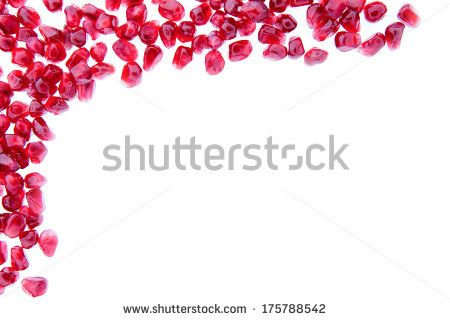 Border of fresh ripe pomegranate seeds arranged in the top left corner and isolated over a white background with copyspace