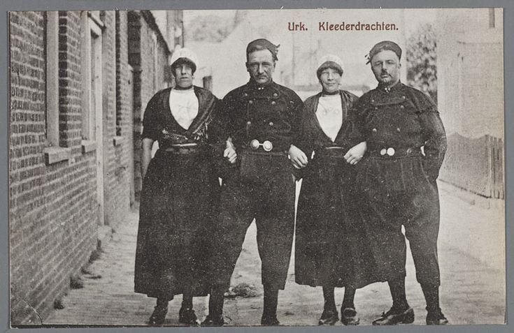 Twee vrouwen en twee mannen in Urker dracht poseren in een straat. De broeksknopen zijn goed te zien. Links is de langsgevel van een woning. 1920-1929 #Urk