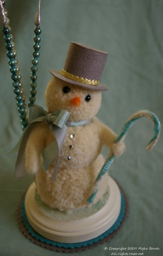 A dapper little fellow! He wears a grey tophat. Blue and sage seam binding ribbon around his neck. He holds a vintage blue and off white