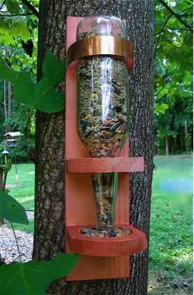 """Sturdy base with copper accent securely holds the over-turned bottle in place, while recessed feeding area keeps seed from spilling out. Works with all types of birdseed mixes and most bottles.  An innovative idea in wild bird feeders that makes a perfect house warming or hostess' gift. Complete with glass bottle, or add your own for a special, one-of-a-kind gift.Handcrafted in the USA Measures 15.5"""" tall x 6"""" deep x 3.75"""" wide Item Weight 2.6 lb."""