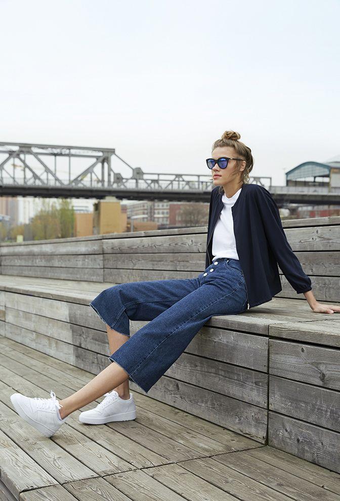 Flared Jeans, weißes T-Shirt, dunkelblaue Jacke, weiße Sneakers, Sonnenbrille