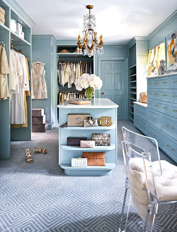 Blue walk in closet features blue built in cubbies over side by side clothes rails facing a blue closet island fitted with shelves illuminated by a French crystal chandelier.