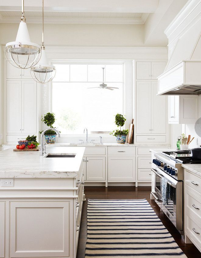 Vintage Modern Farmhouse Kitchen In White Featuring Marble Countertops,  Vintage Industrial Pendant Lights, And