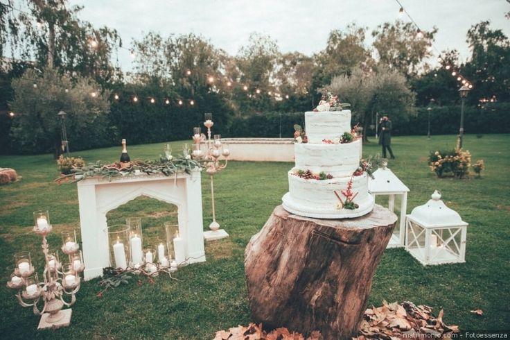 Decorazioni per spazio all'aperto: angolo della torta nuziale con lanterne e candele. Dettagli per esterno per un matrimonio elegante