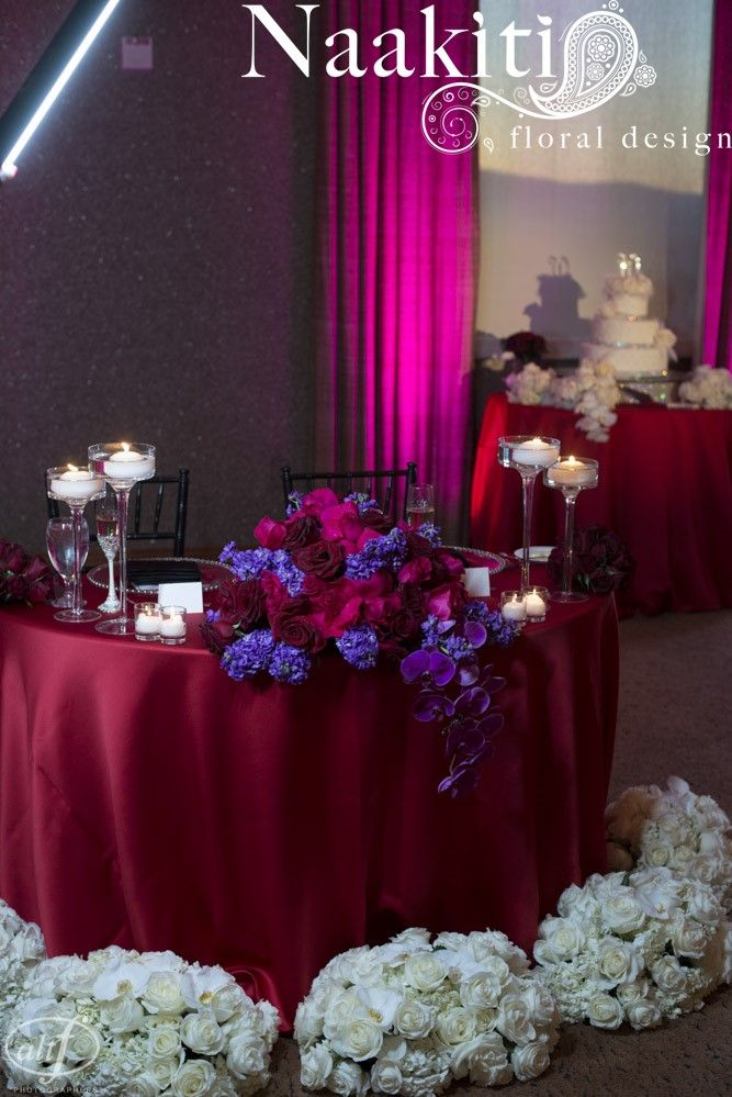 Lush, romantic floral for the sweetheart table. Purple sotck, red roses, phalaenopsis orchids. Photo by #AltfPhotography #NaakitiFloral #SweetheartTable #Candles #Wedding #Romantic #Flowers