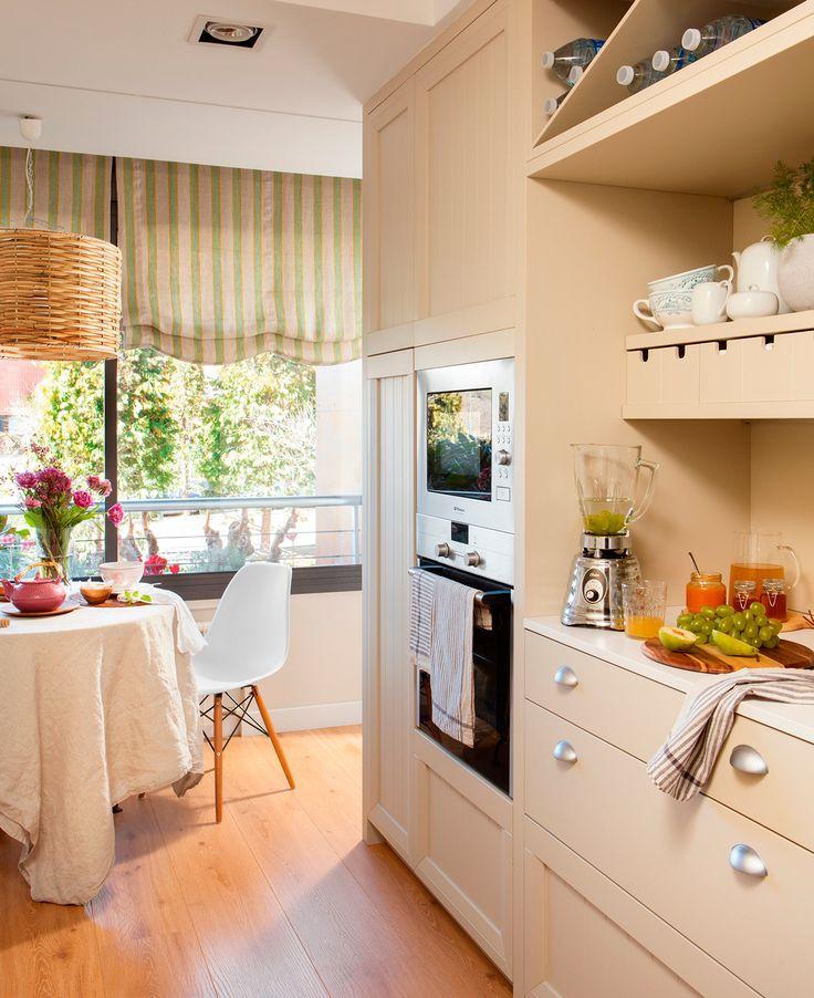 Cocinaoffice con mueble panelado y tiradores, pequeños cajones, suelo de parquet y mesa con sila Eames