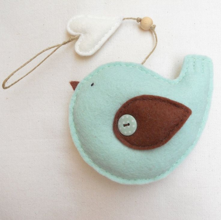 Duckegg blue and brown felt bird with white heart. Made of very soft duckegg blue wool blend felt and filled with polyfill. The little brown wing is stitched to the bird with a polkadot button. The eye is made with a single stitch of black wool thread. A delicate ivory heart and a little wooden bead add a final touch of sweetness.  * The bird measures approx. 12x10cm  * The heart measures approx. 4x5cm (at its widest points)  * It hangs from a 17,5cm hemp twine.€10.00, via Etsy.