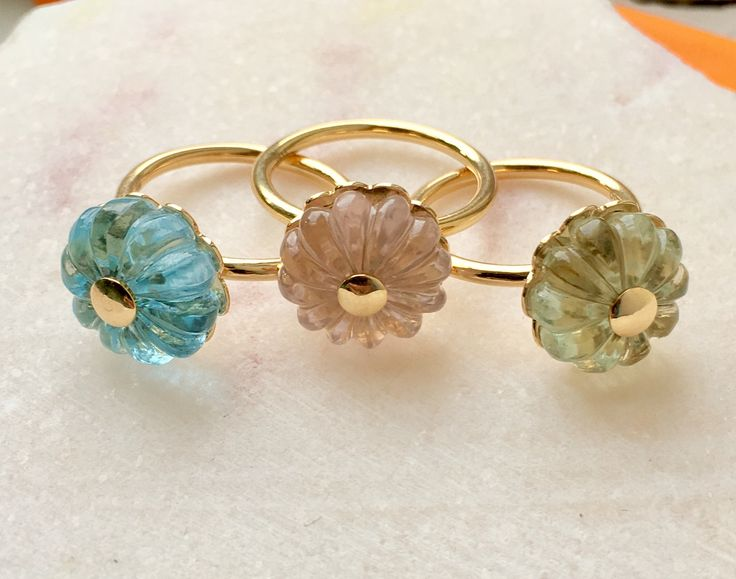 Amazing 18 carat gold rings with blue topaz, green amethyst and rose quartz flowers.