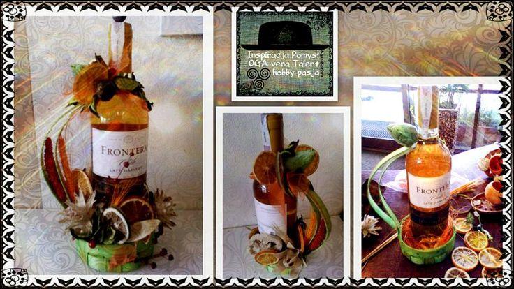 Butelka wina w maleńkim koszyczku ozdobiona suszonymi kwiatami i owocami.