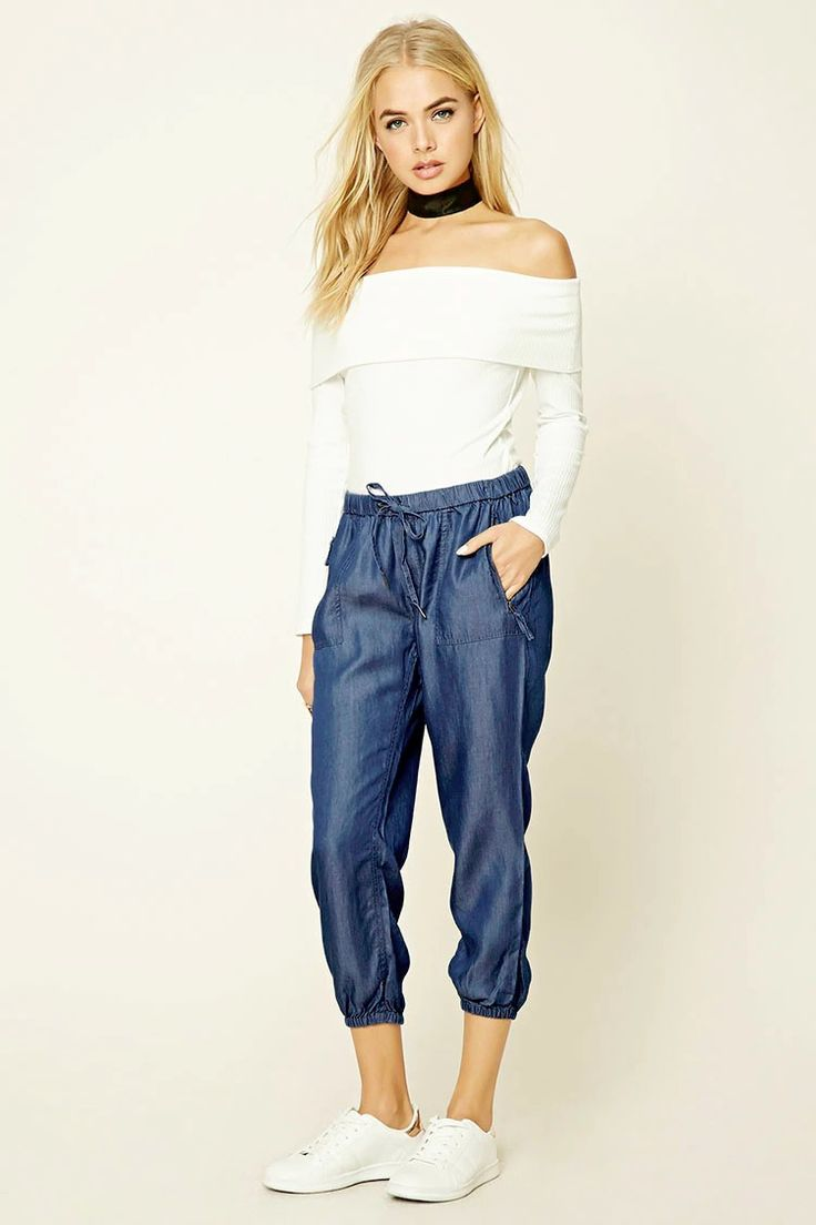 A pair of denim jogger pants featuring an elasticized drawstring waist, a mid-rise, front zip pockets, back patch pocket, and elasticized cuffs.