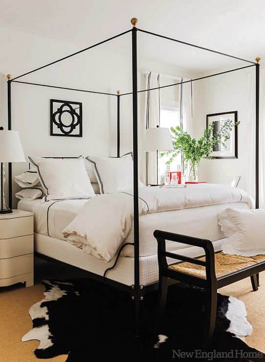 Beautiful black and white bedroom with black iron canopy bed with brass  finials. The bed is .