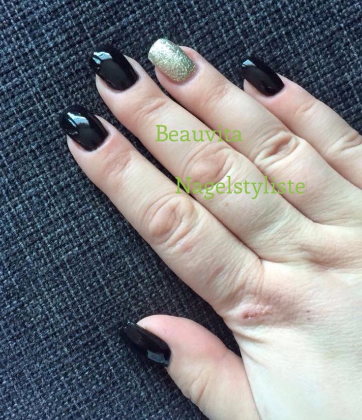 Zwarte gellak met goudkleurige acryl op ringvinger