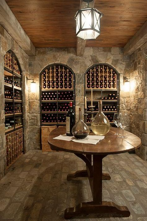 Basement wine room features a wood plank cieling over stone walls fitted with arched wine racks.
