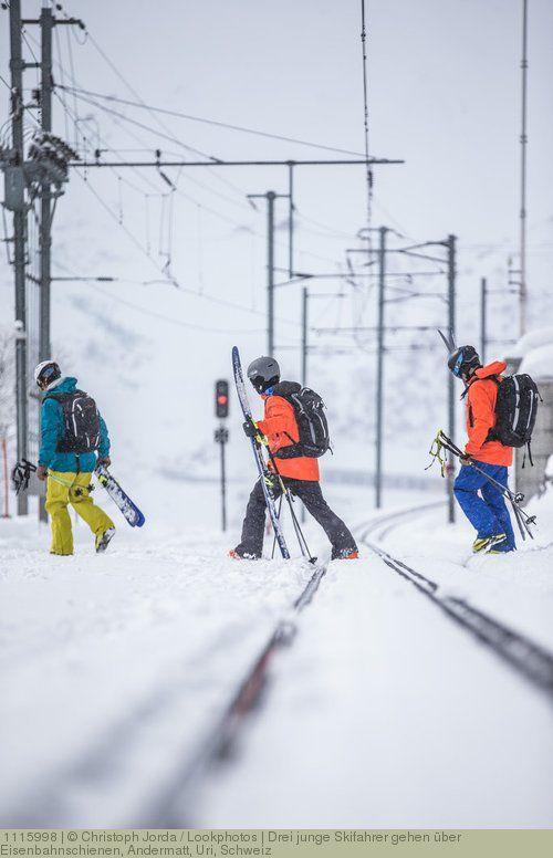 Drei junge Skifahrer gehen über Eisenbahnschienen, Andermatt, Uri, Schweiz