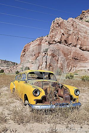 |Vintage car abandoned and rusting away in a desert