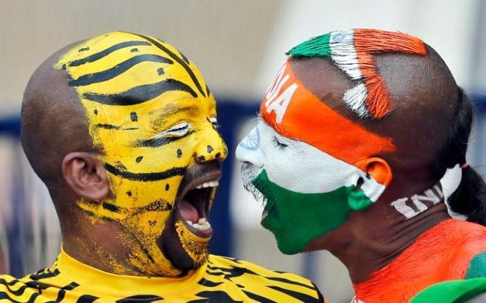 India, right, and Bangladesh cricket fans with faces painted in the colors of their national flags shout to cheer for their teams during the third day of the cricket test match between India and Bangladesh in Hyderabad, India