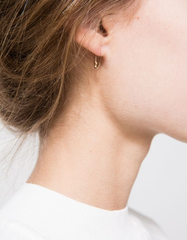 A handcrafted single safety pin earring in Gold from Loren Stewart with a round end.  •Small handcrafted single safety pin earring •Round end •14KT gold •Made in USA