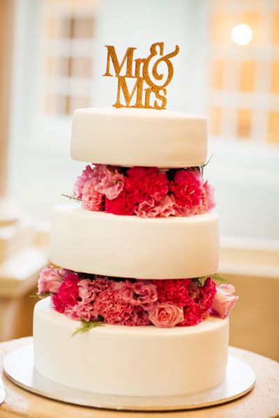 Stylist Tip: The tiers of your wedding cake can be suspended on a stand, leaving space for luxurious layers of flowers in your theme colour. Photo by GM Photographics