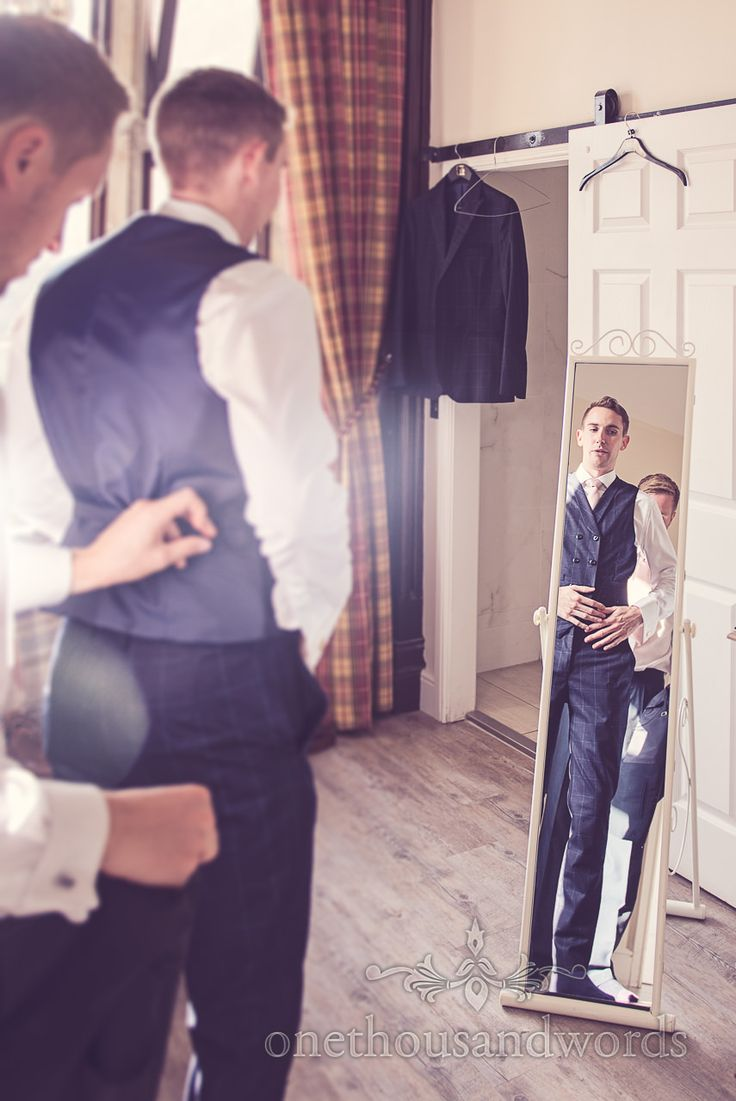 Dapper groom with custom blue wedding suit in full length mirror at Froyle Park wedding. Photography by one thousand words wedding photographers