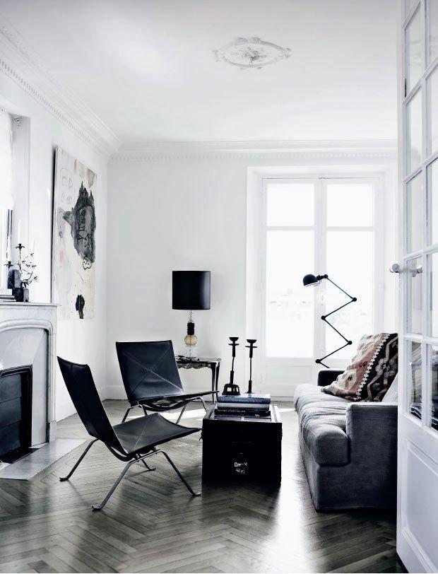 Een witte basis met een houten visgraat-gelegde vloer en zwarte meubels. Mooi evenwicht.