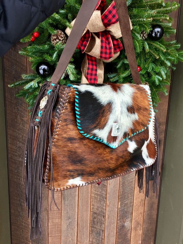 The Micah Bag, with the customers own conchos, hand cut suede fringe, and stitched in brown and turquoise leather lace. Custom purses and totes from gowestdesigns.us