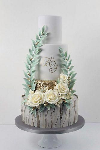 woodland themed wedding cakes bottom layer with gray bark cake white with gold adorned with white flowers and foliage cake trends via instagram