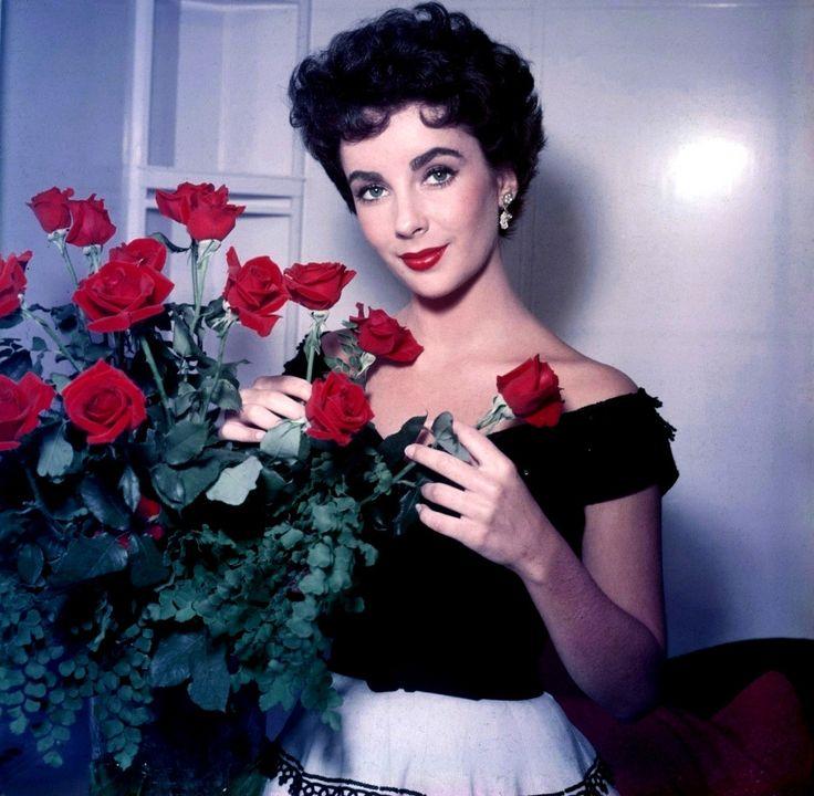 Elizabeth Taylor arranging a bouquet of red roses, 1953.