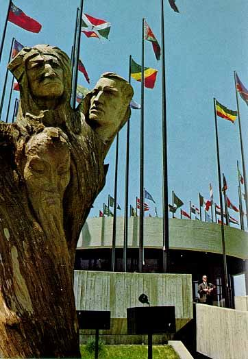 """Expo 67 - United Nations ~ Outside the pavilion's entrance was the Tree of Life. A 150 year-old chestnut tree, 17 feet high and weighing three tons, was pulled from the earth, roots and all, and hollowed out by fire. Joseph """"Peppi"""" Rifesser, a famous woodcarver from Italy carved on the trunk five faces representing peoples of five continents. The haunting visages were a vibrant pleas for equality and unity among men."""