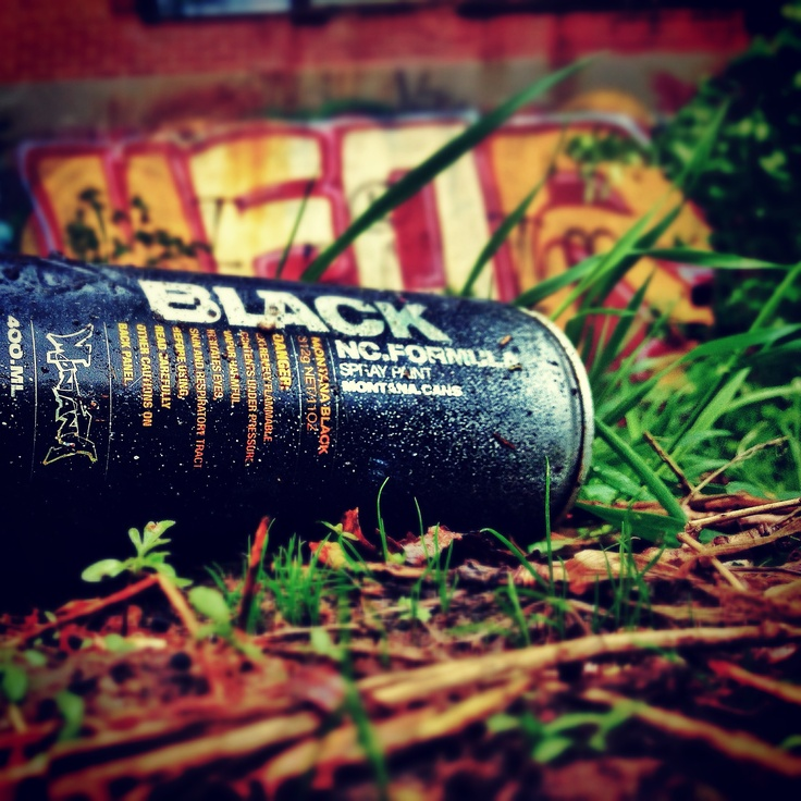 Picture I took with my iPhone of a spraypaint can next to a wall full of graffitis