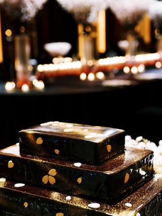 お洒落なデザインは味わいも最高! ウエディング・ケーキもふたりのリクエストに応えるオリジナルを。桜の会場装花に合わせて、チョコレートケーキに花びらを散らして、シックに! 大人のスウィートを表現。
