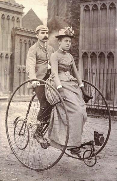 Big wheels. vintage bike. sepia picture. A couple man and woman riding their bike, old fashion bike
