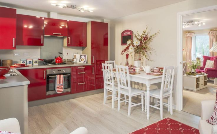 Interior Designed Kitchen Dining Family room, using bold bright Red / Dark Raspberry Gloss kitchen units, white french table and chairs and pale limed oak effect flooring - this room leads on to the cottage raspberry pink living room ! There's a slight 50s feel in here. Barratt Homes 2015.