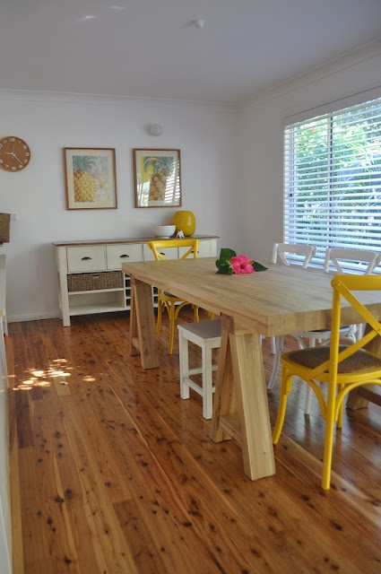 it all works for me, the clock, pineapple prints and yellow chairs.  Airy, fresh and fun!