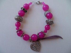 Coeur fuchia, bracelet monté sur fil câblé, fermoir mousqueton couleur argenté. Perles en pâte de verre de couleur fushia et breloques couleur argent vieilli.