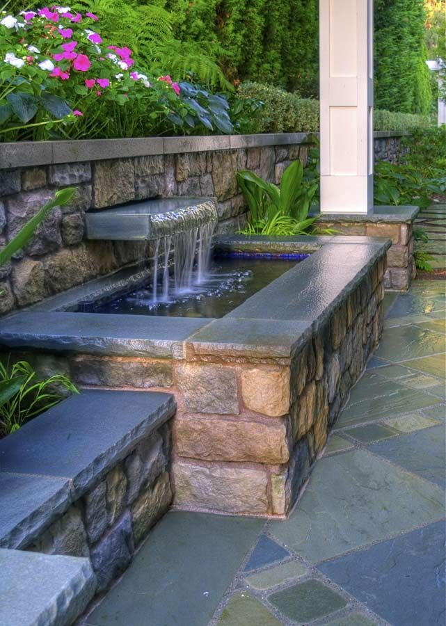 This custom water feature fits nicely into a small or narrow space. I love the chiseled look of the concrete edge.