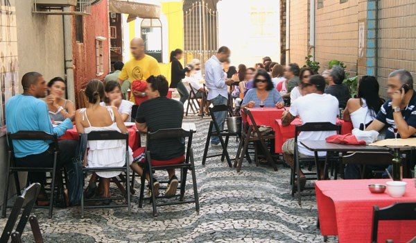 Por Carol Andrade Numa viela estreita, cadeiras e mesas de madeira, com toalhas vermelhas, se espalham ao melhor estilo boteco. Entre elas, o vai e vem dos garçons, levando cerveja gelada e os famo…