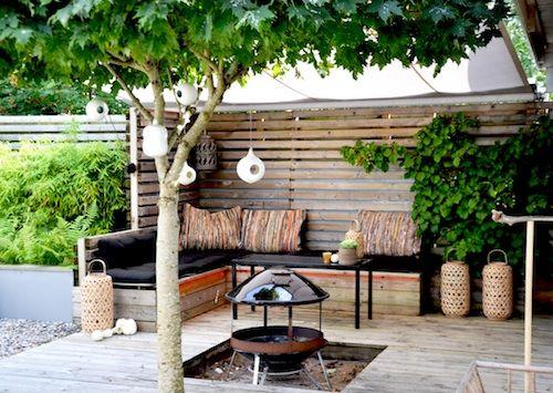 Platsbyggd soffa, spaljé, integrerad grönska och träd, fd sandlådan blir eldplats