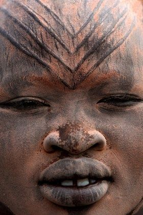 Africa   a close up of a Mundari girl in a cattle camp near Tarakeka; her face has been covered with ocher and ash. On her forehead are some tribal scarification marks. Southern Sudan   © Bruno Zanzottera.