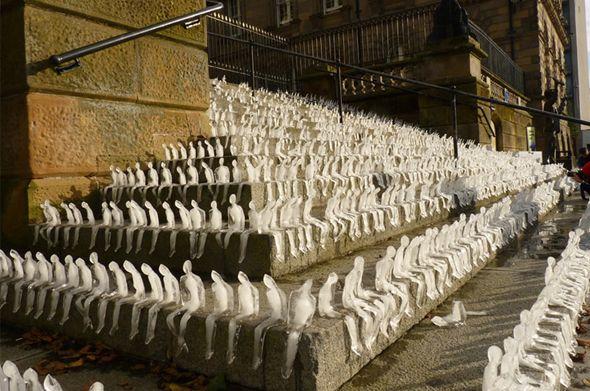 Artiste brésilien, Nele Azevedo signe une nouvelle installation urbaine dans le cadre de son projet Minimum Monument et à l'occasion du Belfast Festival. Son oeuvre éphémère est composée de centaines de figurines humaines en glace, en position assise qui ont été placées le long des marches d'un monument.
