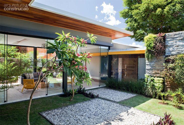 O paisagismo age como extensão do projeto arquitetônico. A linguagem geométrica do piso de pedriscos e grama se repete no jardim vertical, com diferentes espécies, como samambaia, véu-de-noiva e aspargo-pendente.